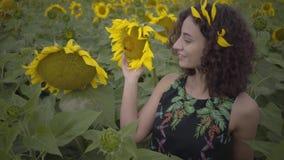 Powabny kędzierzawy kobiety odprowadzenie na słonecznikowym polu Jaskrawy ? zbiory wideo