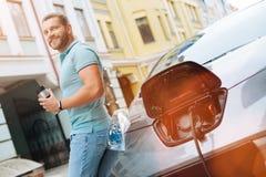 Powabny mężczyzna pije kawę podczas gdy samochód ładuje zdjęcia stock