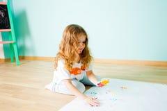 Powabny mała dziewczynka obraz używać ona palce podczas gdy siedzący na podłodze zdjęcia royalty free