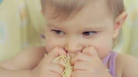 Powabny małej dziewczynki łasowania spaghetti z ona palce i cieszyć się je zdjęcie wideo