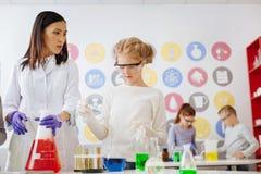 Powabny nauczyciela i dziewczyny dyrygentury chemiczny eksperyment wpólnie zdjęcia royalty free