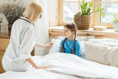 Powabny pediatra stawia małej chorej dziewczyny łóżko obrazy stock