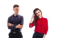 Powabny poważny facet warty ręki spinać blisko pięknej dziewczyny z czerwoną pomadką i czerwieni bluzką Obrazy Stock