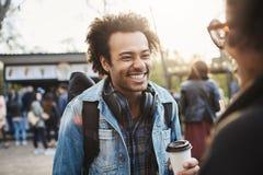 Powabny szczęśliwy chłopak z afro fryzurą uśmiechniętą i roześmianą podczas gdy opowiadający dziewczyna i pijący kawę wewnątrz fotografia stock