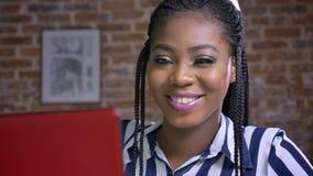 Powabny uśmiechu i afrykanina bizneswoman który pracuje na jej czerwonym laptopie w biurze