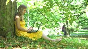 Poważna kobieta pracuje z laptopu i pary odprowadzeniem w parku na tle 4K zbiory wideo