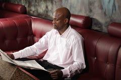 Poważny afrykański mężczyzna czytania papier Fotografia Stock