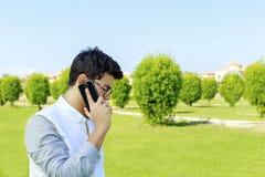 Poważny młody człowiek opowiada na telefonie komórkowym Obrazy Stock