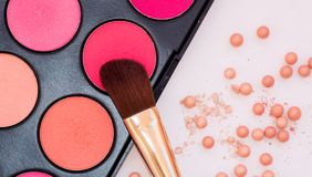 Powder in the balls with a radiant effect on the background of the set for blush. Make-up cosmetics brush. Royalty Free Stock Photography