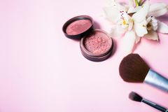 Powder, brush and flower on pink background.  Royalty Free Stock Image