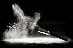 A powder brush and white loose powder Royalty Free Stock Image