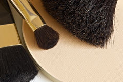 Powder and brushes. Compact powder and make-up brushes, close-up, shallow DOF (at powder Royalty Free Stock Photos