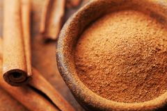 Powder cinnamon and sticks and on brown rustic background. Aromatic spices. Stock Images