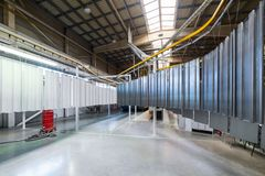 Powder coating line. Metal panels are suspended on an overhead conveyor line. Painting products in an electrostatic royalty free stock photo