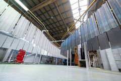 Powder coating line. Metal panels are suspended on an overhead conveyor line. stock photography