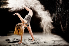 Powder contemporay dancer. Expressive dance movement of a female contemporary ballet dancer on a black background and with white powder royalty free stock photo
