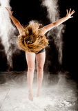 Powder contemporary dancer. Expressive dance movement of a female contemporary ballet dancer jumping on stage with a black background and with white powder Royalty Free Stock Photo
