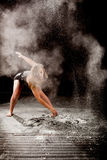 Powder contemporay dancer. Expressive dance movement of a female contemporary ballet dancer on stage with a black background and with white powder Stock Photo