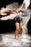 Powder contemporary dancer. Expressive dance movement of a female contemporary ballet dancer on stage with a black background with white power and hair around Stock Image