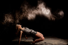 Powder dancer action low key. Dance expressive dance movement of a female contemporary dancer in low-key with white powder on a black background looking in the royalty free stock images