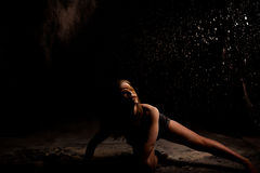 Powder dancer action low key. Dance expressive dance movement of a female contemporary dancer in low-key with white powder on a black background looking in the royalty free stock photography