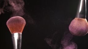 Powder explosion with 2 beauty brushes. On a black background stock footage