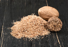 Nutmeg powder. Powder of nutmeg with nuts on wooden background royalty free stock photos