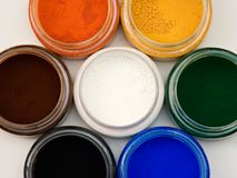 Powder pigments. Top view of natural earth pigments pots stock images