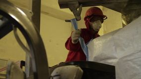 Powder production at the factor. Scene. Man pours a loose substance in a bag after production at the plant.  stock footage