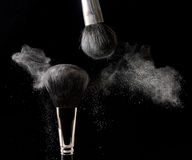 Powder Room. Powder is rubbed off two cosmetics brushes over a black background Royalty Free Stock Photos