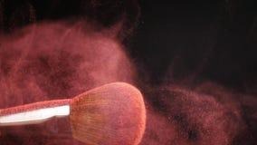 Powderbrush på svart bakgrund med rosa färgpulver arkivfilmer