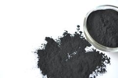 Powdered activated charcoal in a glass bowl and sprinkled around. Powdered activated charcoal in a glass bowl Stock Image