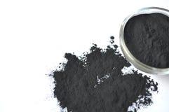 Powdered ativou o carvão vegetal em uma bacia de vidro e polvilhado ao redor imagem de stock