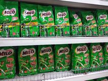 Powdered chocolate drinks in commercial packaging are displayed on shelves inside the store.