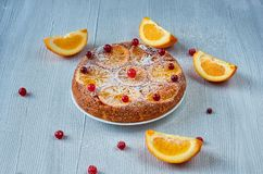 Powdered citrus pie with caramelized oranges and fresh red berries on the gray surface. Sweet orange pie with raw orange slices. And cranberries on the gray Stock Image