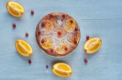 Powdered citrus pie with caramelized oranges and fresh red berries on the gray table. Orange pie decorated with raw orange slices. And cranberries on the gray Stock Photography