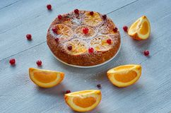 Powdered citrus pie with caramelized oranges and fresh red berries on the gray table. Orange pie decorated with raw orange slices. And cranberries on the gray Stock Image