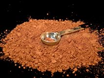 Powdered Cocoa with Teaspoon. Close up color photograph of rich, brown powdered cocoa with a stainless steel teaspoon laying in the middle of it.  Black Stock Photo