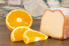 Powdered lemon cake with fresh sliced orange fruits on a wooden Stock Photography