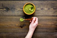 Powdered matcha green tea in bowl on dark wooden background top view copy space. Powdered matcha green tea in bowl on dark wooden background top view Royalty Free Stock Photo