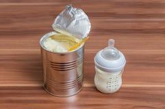 Powdered mjölkar formel kan in och flaskan för matning behandla som ett barn på trätabellen Royaltyfri Foto