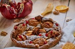 A powdered pear pie decorated with white cloth, fresh sliced pears and pomegranate, dried oranges, walnuts, anise stars. On the wooden board. Healthy homemade stock image