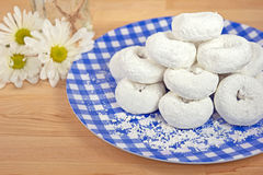 Powdered sugar donuts. Pile of powdered sugar donuts on a blue and white gingham plate with daisy bouquet Royalty Free Stock Images