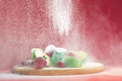 Powdered sugar falling on fresh fruits. Royalty Free Stock Photo