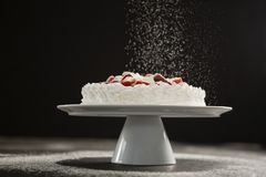 Powdered sugar falling over white cake on stand. Against black background Royalty Free Stock Images