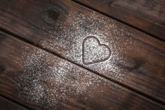 Powdered sugar heart on wooden background. Shape of a heart with powdered sugar on wooden background Royalty Free Stock Photo