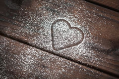 Powdered sugar heart on wooden background. Shape of a heart with powdered sugar on wooden background Stock Photography