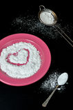 Powdered sugar. In plate with spoon and sieve on black background Stock Photo
