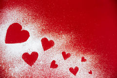 Powdered sugar scattered in the form of heart. On red background royalty free stock image
