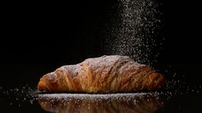 Powdered sugar sprinkling onto a croissant stock footage